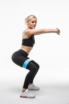 Uma linda e muito jovem loira está fazendo diferentes exercícios actobatic de alongamento de braços e pernas em branco