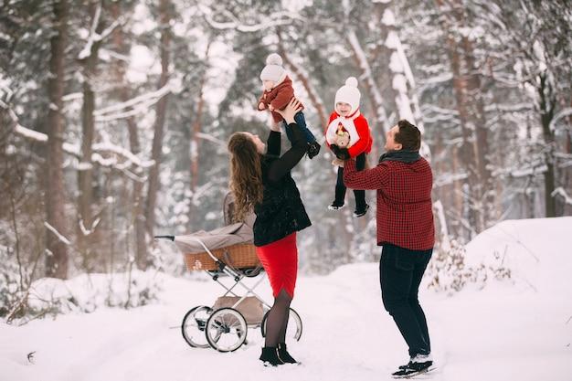 Uma linda família com carrinho de bebê retrô caminha pela floresta de inverno nevado. mãe, pai, filha e filho a gostar do dia ao ar livre. feriados, natal, felicidade juntos, infância apaixonada.