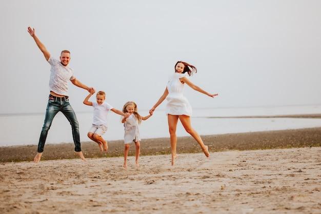 Uma linda família com dois filhos em roupas de cores claras salta