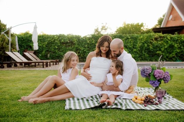 Uma linda família com duas filhas e uma mãe grávida em um piquenique