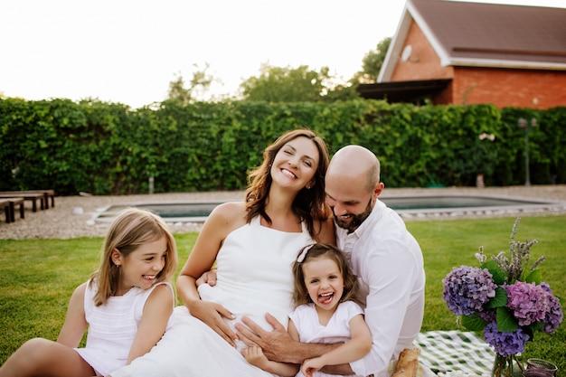 Uma linda família em roupas brancas rindo no fundo da piscina