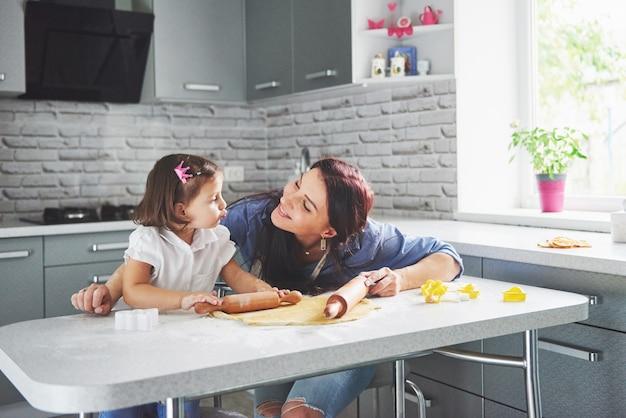 Uma linda filha com a mãe dela cozinhando na cozinha