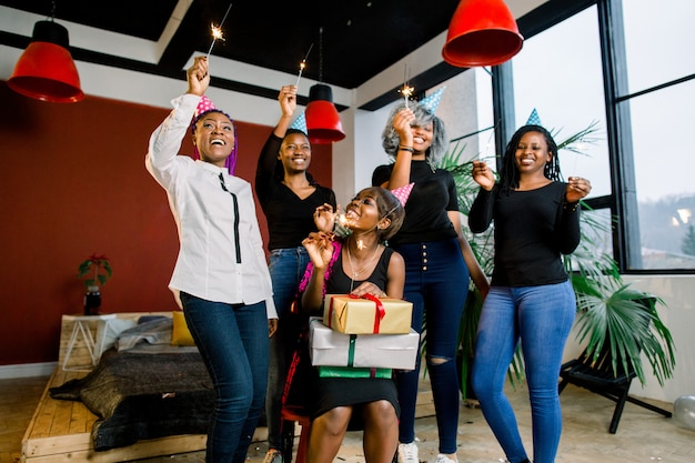 Uma linda garota africana sorridente tem presentes nas mãos e comemora aniversário com os amigos. as meninas têm luzes de bengala nas mãos