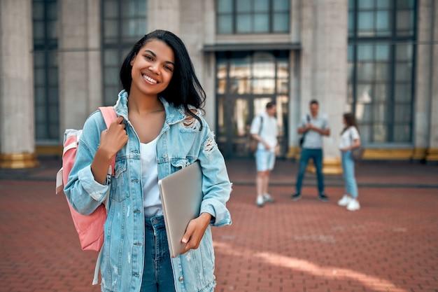 Uma linda garota afro-americana com uma mochila e um laptop perto do campus