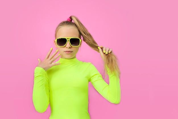 Uma linda garota alegre de óculos escuros em um fundo colorido