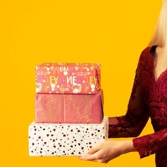 Uma linda garota asiática em um vestido vermelho, segurar nos presentes de mãos. comemoração de natal ou ano novo