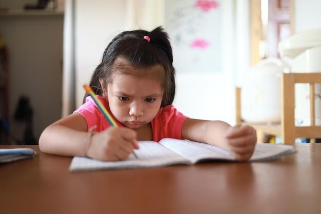 Uma linda garota asiática fazendo lição de casa em sua casa durante o dia