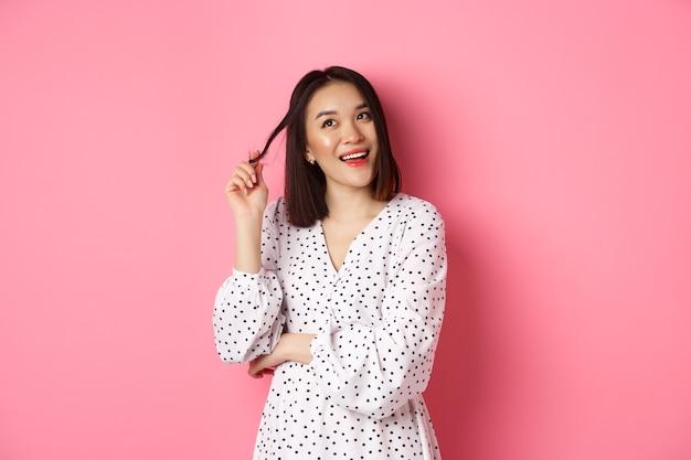 Uma linda garota asiática sonhadora pensando em fazer compras e sorrindo, olhando no canto superior esquerdo com o pensamento ...