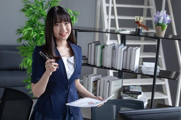 Uma linda garota asiática vestindo um terno azul escuro, em pé no escritório em um escritório moderno e olhando para documentos de arquivo e na frente é uma grande janela de vidro.