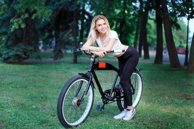 Uma linda garota atlética com uma bicicleta no parque sorri e posa para a câmera