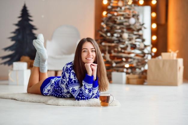 Uma linda garota atraente em uma camisola de malha fica em um tapete branco