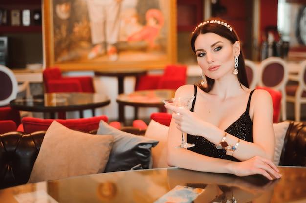 Uma linda garota bebe martini no lobby do hotel e está esperando seu jovem namorado