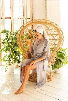Uma linda garota bebe suco de laranja. ela está sentada em uma cadeira de vime de madeira. interior do apartamento estilo boho