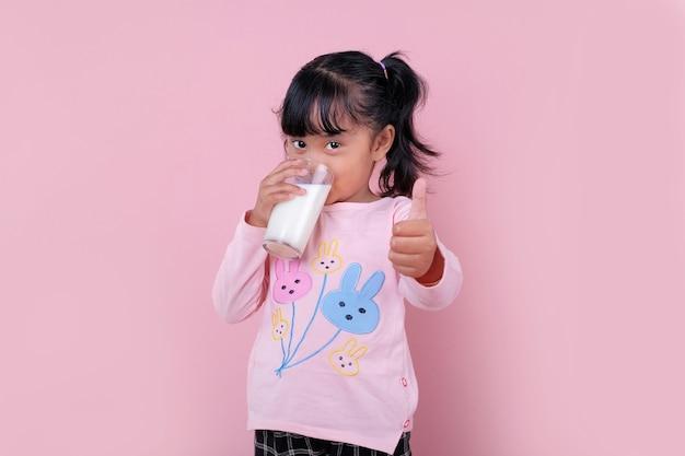 Uma linda garota bebendo de um copo de leite