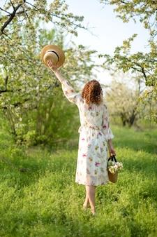 Uma linda garota caminha em um jardim primavera. o conceito de unidade do homem com a natureza.