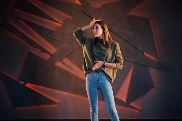 Uma linda garota coloca o fotógrafo no fundo de uma parede preta e uma luz de fundo vermelha.