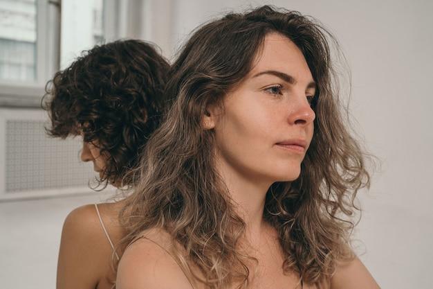 Uma linda garota com cabelos cacheados olha no quadro uma garota sem maquiagem uma linda e natural ...