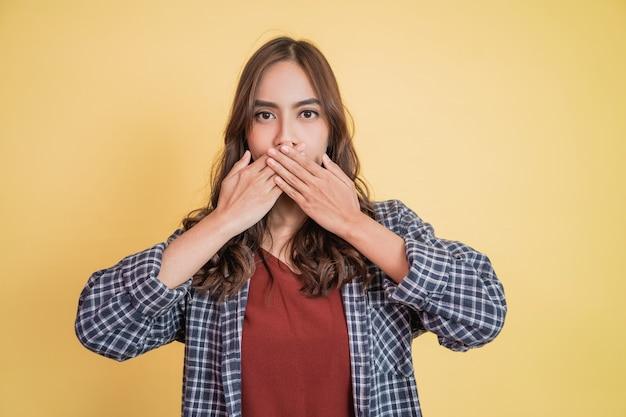 Uma linda garota com cabelos longos cobrindo a boca com as duas mãos