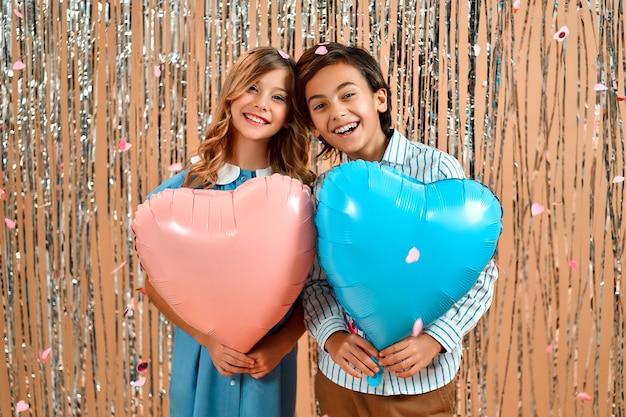 Uma linda garota com cachos em um vestido azul e um bom garoto em uma camisa estão segurando balões de corações dos namorados isolados com uma cortina brilhante.