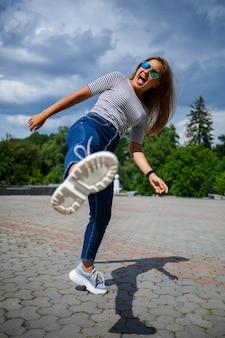 Uma linda garota com longos cabelos loiros de aparência europeia. vestido com jeans e uma camiseta. caminhe em um dia ensolarado