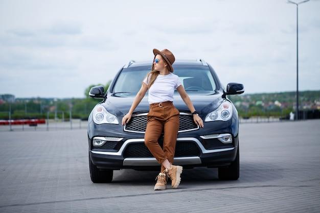 Uma linda garota com óculos e um chapéu marrom está de pé perto de um carro preto. mulher jovem com carro no estacionamento