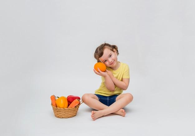 Uma linda garota com rabos de cavalo sorri e segura uma laranja nas mãos perto do rosto. uma menina está sentada com uma cesta de legumes e frutas em um espaço em branco. copie o espaço.