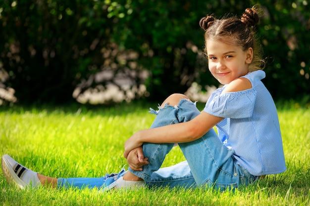 Uma linda garota com roupas azuis na natureza no verão no parque. garoto na moda. foto de alta qualidade
