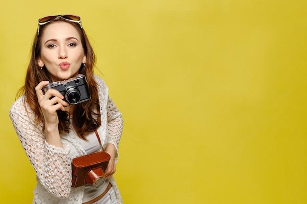 Uma linda garota com roupas casuais com uma câmera vintage olha para a câmera e manda um beijo.
