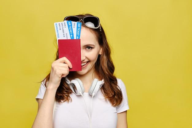 Uma linda garota com roupas casuais detém um passaporte e passagens aéreas cobrindo metade do rosto.