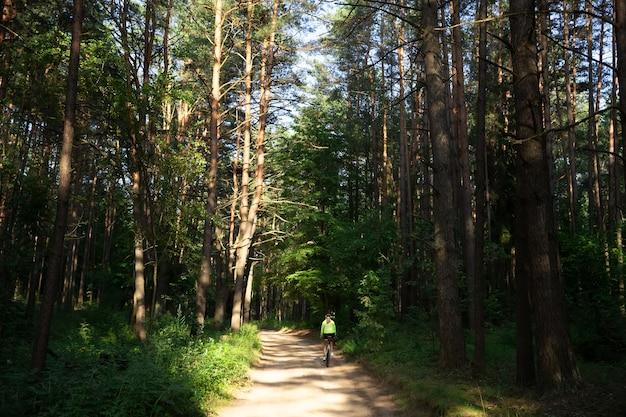 Uma linda garota com um blusão verde brilhante, shorts e um capacete anda de bicicleta na floresta