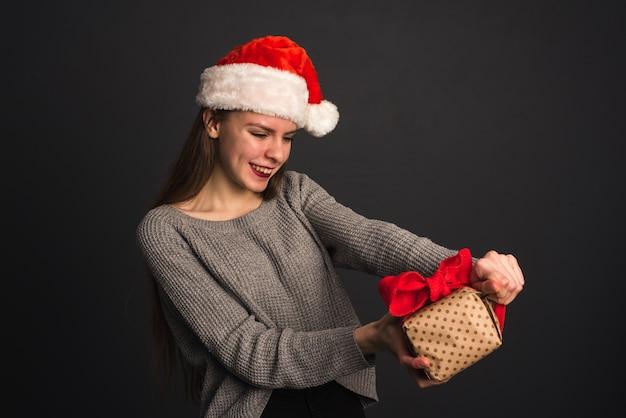 Uma linda garota com um chapéu de papai noel em uma parede cinza escura abre um presente de natal e quebra a embalagem de presente da kraft.