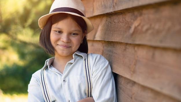 Uma linda garota com um chapéu e uma camisa com suspensórios fica encostada em uma casa de madeira ou um celeiro