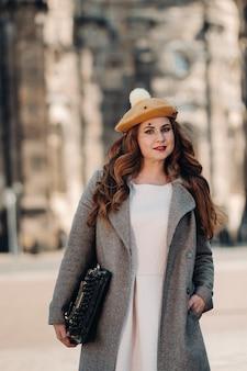 Uma linda garota com um chapéu parada com uma máquina de escrever na cidade velha de dresden