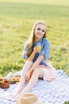 Uma linda garota com um copo de suco espremido na hora se senta em um cobertor em um piquenique de verão e sorri um sorriso encantador