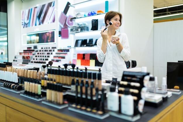 Uma linda garota com um corte de cabelo curto faz maquiagem com pó facial.