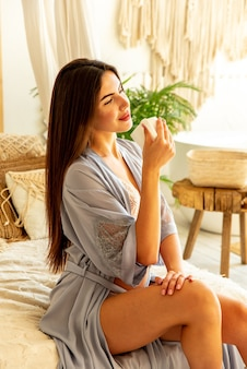 Uma linda garota com um manto azul aproveita a manhã ao amanhecer. bebe café ou chá em uma xícara branca e se senta no sofá.