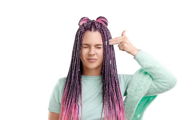 Uma linda garota com um penteado de tranças rosa em roupas turquesa dá um tiro na cabeça com os dedos. o conceito de fadiga, obsessão, negatividade.
