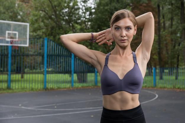 Uma linda garota com um top esportivo e legging treina em uma quadra de basquete no parque