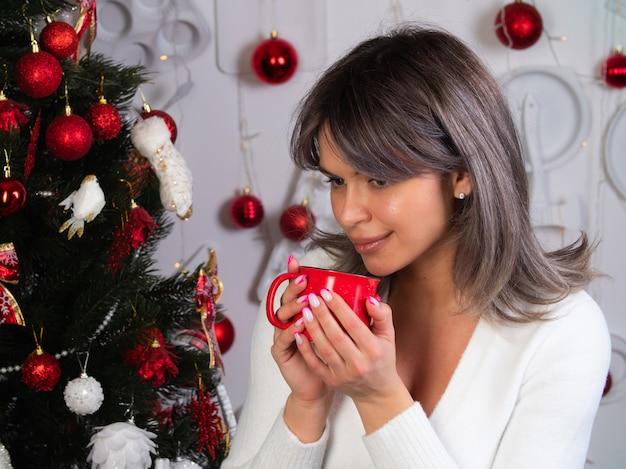 Uma linda garota com uma caneca vermelha nas mãos encontra o ano novo e o natal na árvore de natal
