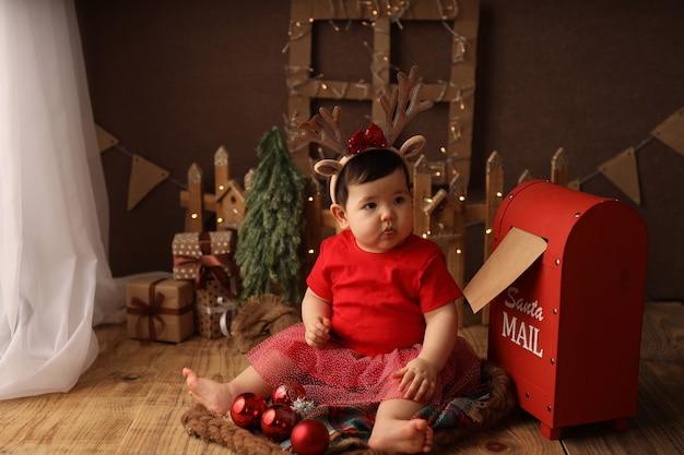 Uma linda garota com uma fantasia de natal vermelha envia uma carta ao papai noel