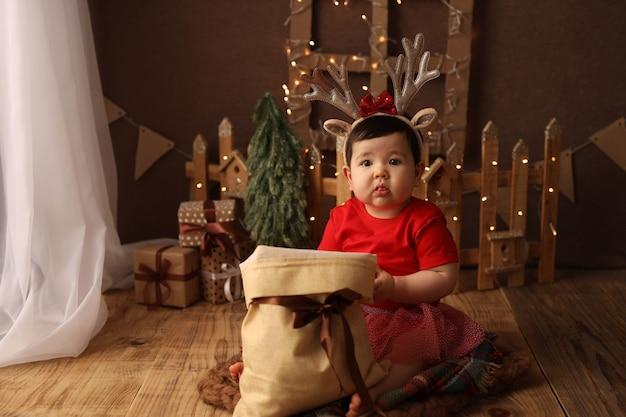Uma linda garota com uma fantasia de natal vermelha tira brinquedos da árvore de natal de uma bolsa com presentes