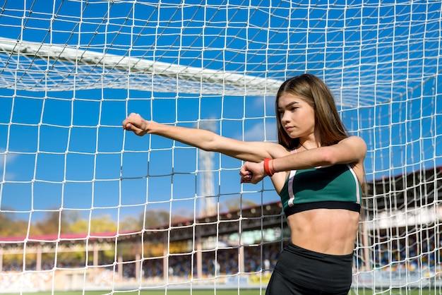 Uma linda garota com uma figura perfeita está perto de um gol de futebol no estádio. fitness e conceito de estilo de vida saudável.