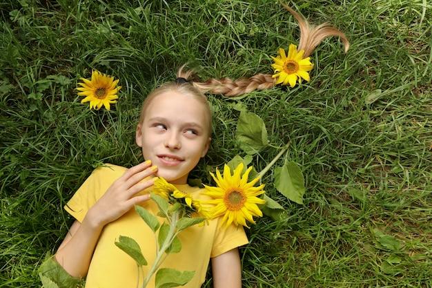 Uma linda garota com uma manicure amarela deitada na grama com girassóis