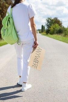 Uma linda garota com uma mochila no ombro segura uma placa com a inscrição em qualquer lugar. pegar carona, aventura.