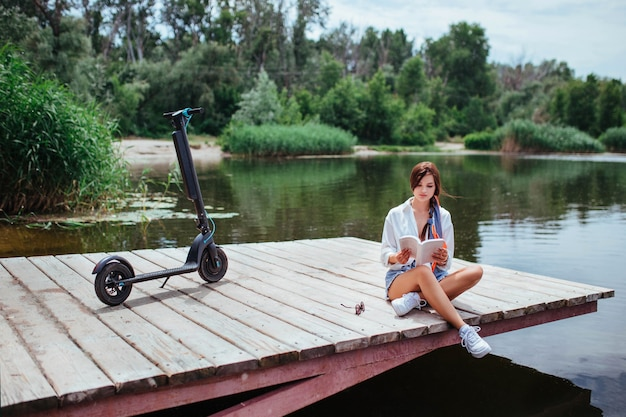 Uma linda garota com uma scooter elétrica lê um livro sobre uma ponte de madeira à beira do rio. transporte ecológico e conceito de saúde.