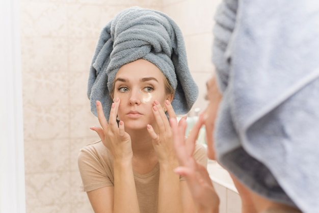 Uma linda garota com uma toalha na cabeça coloca manchas de hidrogel sob os olhos no rosto.