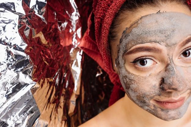 Uma linda garota com uma toalha vermelha na cabeça aplicou uma máscara de argila no rosto, ao lado do papel alumínio