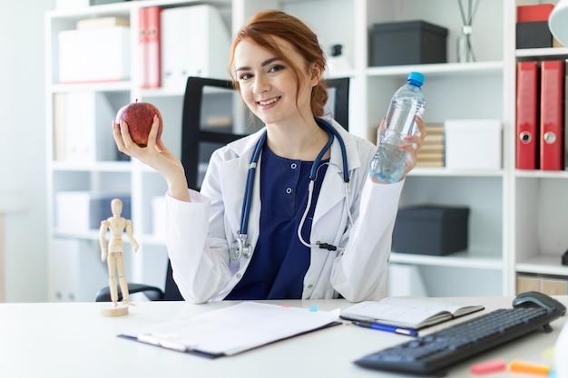 Uma linda garota com uma túnica branca se senta em uma mesa no escritório e tem uma maçã e uma garrafa de água na mão.