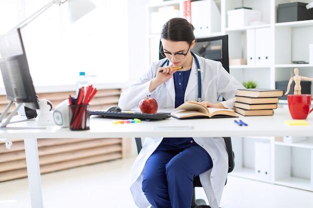 Uma linda garota com uma túnica branca senta-se em uma mesa de computador, segura uma caneta e trabalha com um caderno e documentos.