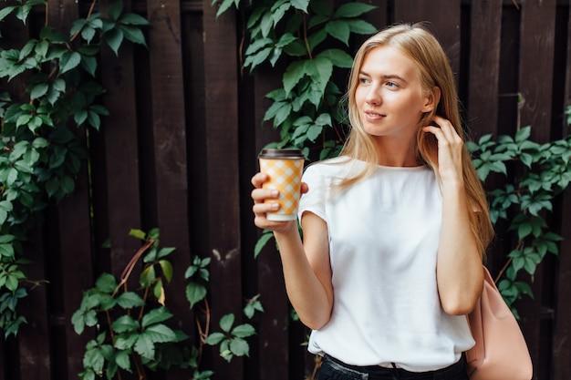 Uma linda garota com uma xícara de café, vestida com uma camiseta branca, fica ao ar livre, na parede decídua de madeira, bebendo uma bebida